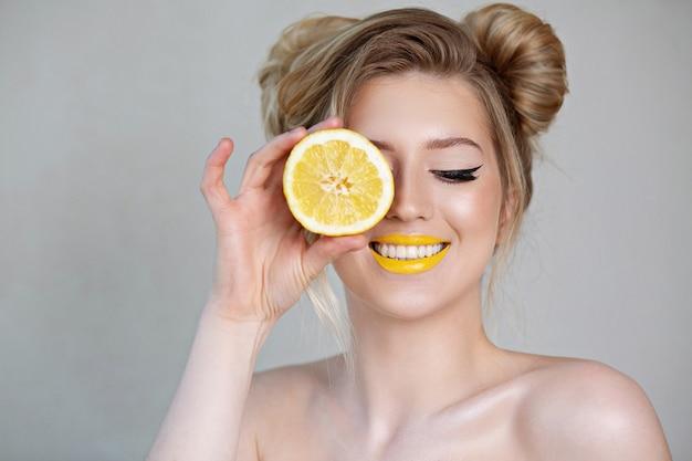 그녀의 얼굴 근처에 레몬을 들고 쾌활 한 금발 소녀입니다. 회색 배경에 스튜디오 촬영