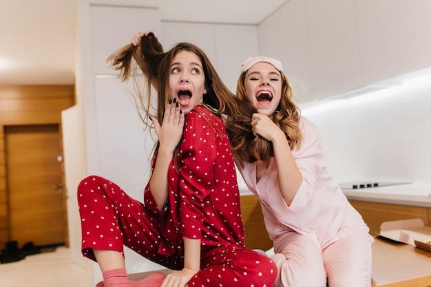 友達の髪の毛で遊んで笑っているsleepmaskの陽気なブロンドの女の子。朝食前に浮気しているのんきな白人姉妹の屋内肖像画。