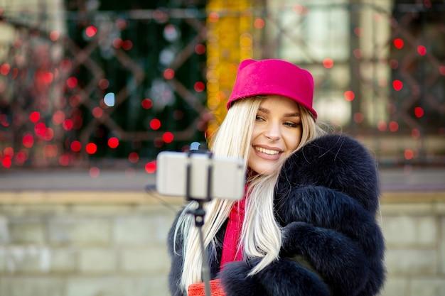 スマートフォンで自画像を作る陽気なブロンドの女の子