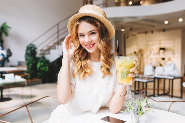 Веселая блондинка с бокалом фруктового коктейля расслабляется в кафе с современным интерьером и нежно улыбается