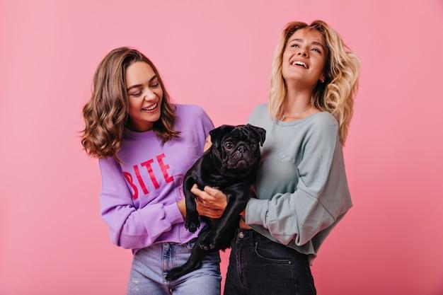 黒の面白い子犬を保持している幸せな表情を持つ陽気なブロンドの女の子。彼女のペットを笑顔で見ているブルネットの女性モデルの屋内の肖像画。