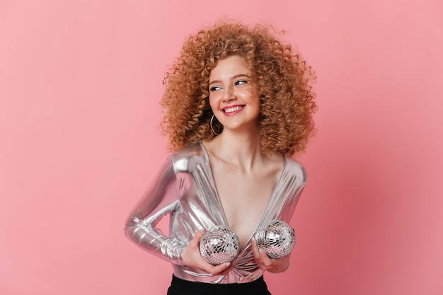 Cheerful blonde girl with voluminous curly hairstyle laughs and holds two disco balls near her breast.