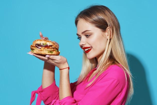 Веселая блондинка в розовой рубашке гамбургер фаст-фуд закуска синий фон