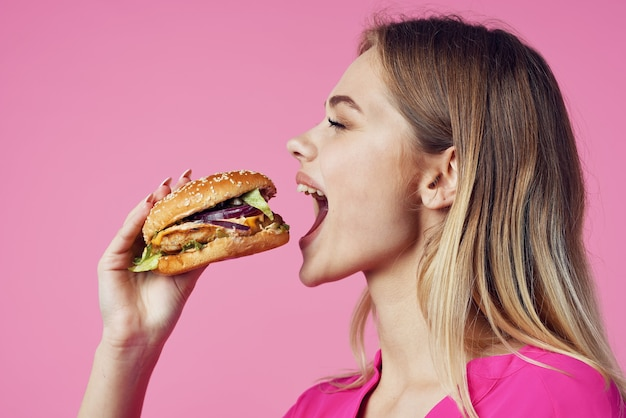 Веселая блондинка в розовой рубашке гамбургер закуска быстрого питания
