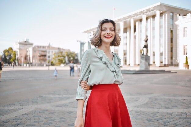 ストリートウォークライフスタイルの赤いスカートで陽気なブロンド