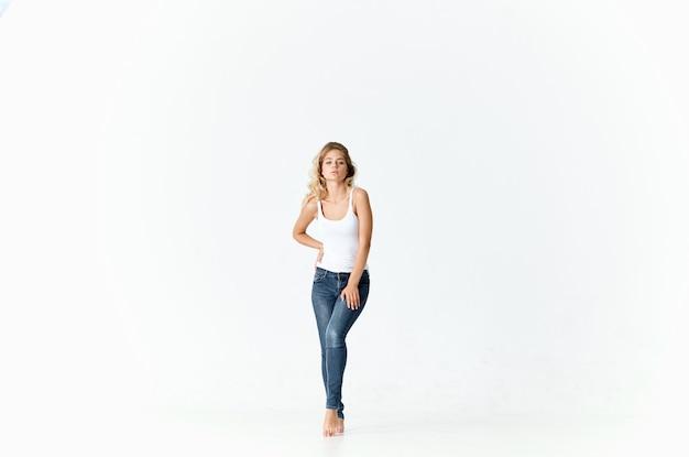 Веселая блондинка в белой майке танцует движение энергии
