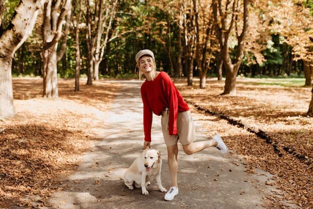 Жизнерадостная блондинка в стильном красном пуловере и бежевых шортах веселится в красивом осеннем парке со своей собакой.