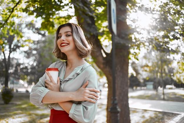公園の木々の陽気なブロンドは、コーヒーの残りのカップ。高品質の写真