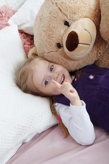 쾌활한 금발 소녀는 큰 부드러운 장난감 곰에 누워