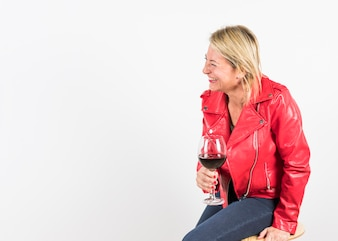 Cheerful blonde mature woman sitting on stool holding red wine glass in hand
