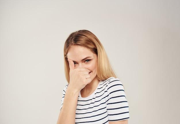 Жизнерадостная блондинка на светлом фоне показывает пальцем и просматривается укороченная футболка в полоску. фото высокого качества