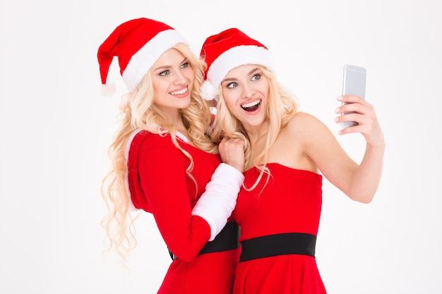 빨간 산타 클로스 옷과 모자에 밝은 금발 자매 쌍둥이 흰색 배경 위에 크리스마스 트리 근처 포즈 숨기기