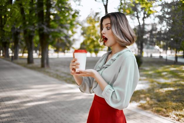 公園を歩いて屋外でコーヒーを飲みながら陽気なブロンド