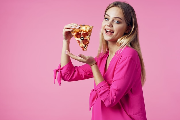 Cheerful blonde with pizza in her hands junk food snack pink background