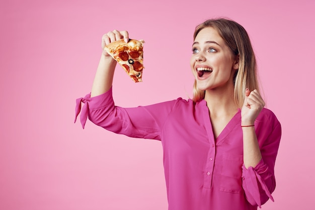 彼女の手にピザと陽気なブロンドジャンクフードスナックピンクの背景