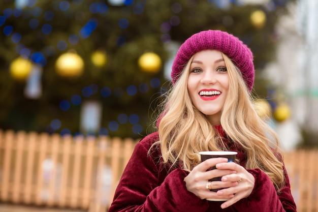 キエフの中央広場にあるクリスマスツリーの近くでコーヒーを飲む陽気なブロンドの女性