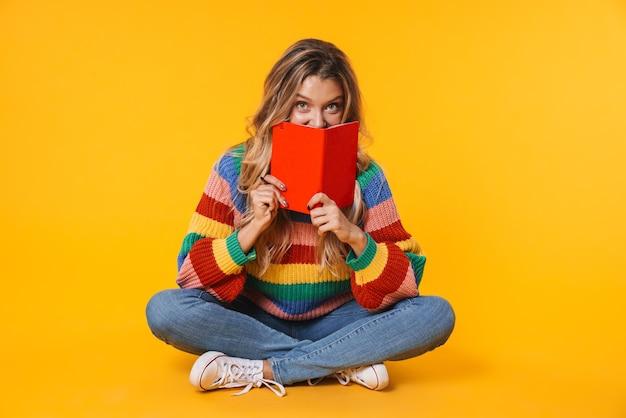Веселая блондинка держит дневник, сидя на полу, изолированном над желтой стеной