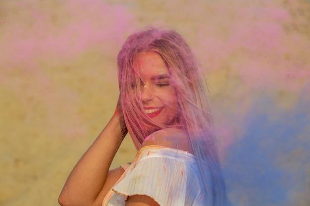 砂漠でピンクとブルーのドライペイントホーリーで遊ぶ陽気なブロンドの女性