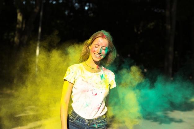 公園で黄色と緑のドライペイントホーリーで遊ぶ陽気なブロンドの女性