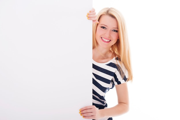 Cheerful blonde woman pointing at blank whiteboard