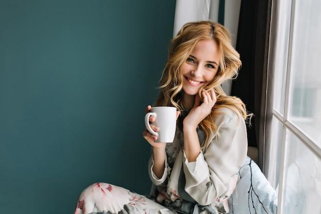 Веселая блондинка расслабляющий и сидя на подоконнике, держа чашку кофе, чая. у нее длинные светлые волнистые волосы, красивая улыбка. носить красивую пижаму в цветах.