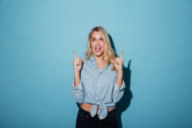 A cheerful blonde woman in shirt pointing up