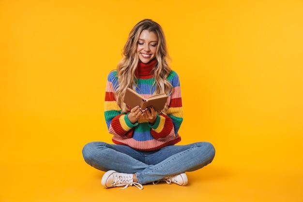 Веселая блондинка улыбается и читает книгу, сидя на полу, изолированном над желтой стеной