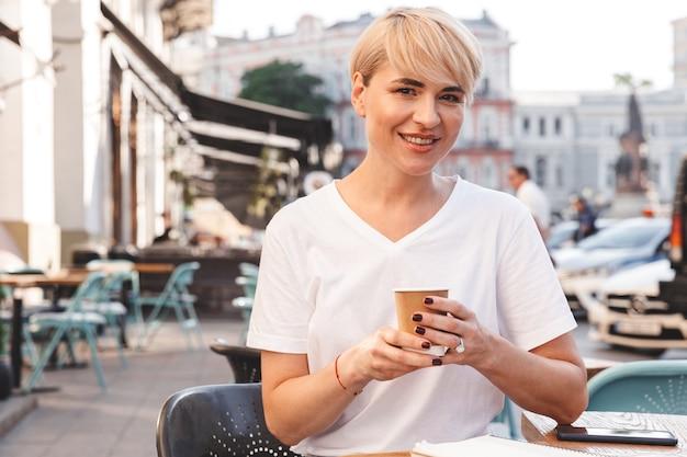 夏にストリートカフェに座って、紙コップからコーヒーを飲む白いtシャツを着て陽気なブロンドの女性