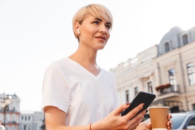 屋外の夏のカフェに座って紙コップからコーヒーを飲みながら、携帯電話とワイヤレスイヤホンを使用して白いtシャツを着ている陽気なブロンドの女性