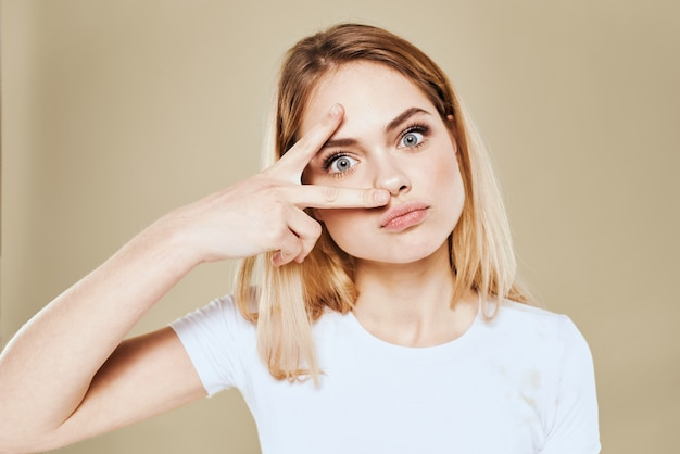 Cheerful blonde woman in a white t-shirt gestures with her hand emotions beige background.