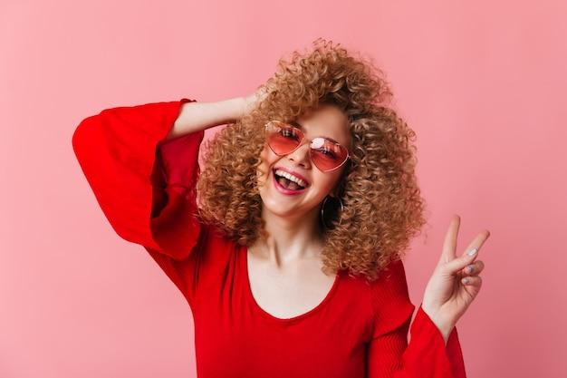 カールのある陽気なブロンドの女性は笑い、ピンクのスペースにピースサインを示しています。サングラスと赤いトップの女性のスナップショット。