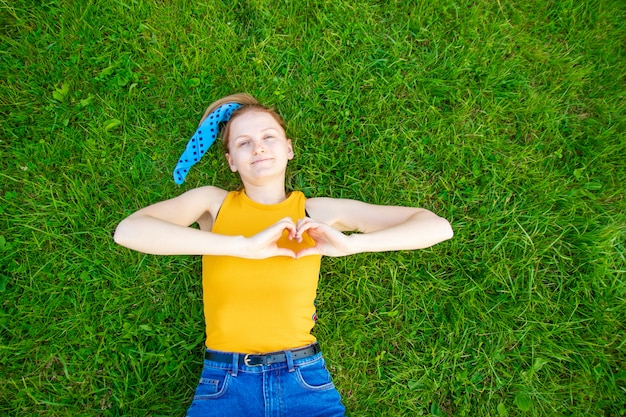 Cheerful blonde young woman makes a heart sign with her hands and lies on green grass