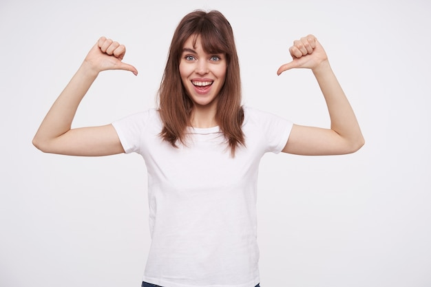 Cheerful blue-eyed lovely young brown haired lady smiling widely while showing on herself with raised hands, wearing basic white t-shirt while standing over white wall