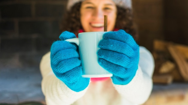 Cheerful blurred woman showing hot beverage