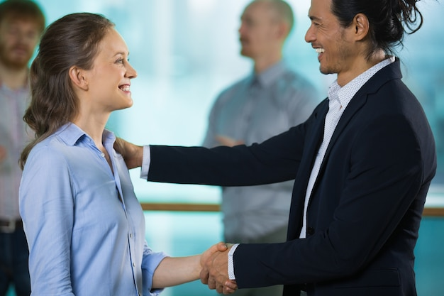 Cheerful boss congratulating new employee