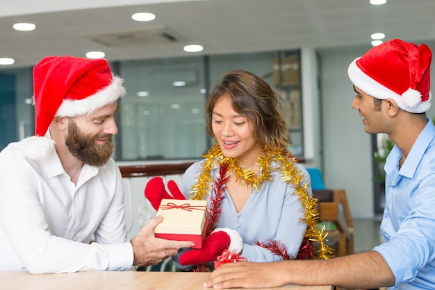 Cheerful boss giving christmas gifts to employees