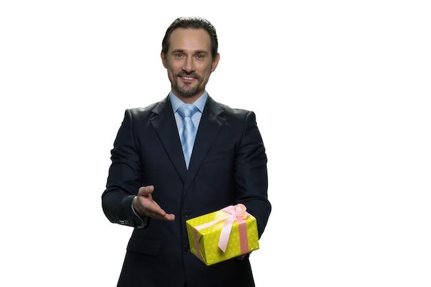 노란색 상자에 선물을 들고 명랑 보스. 현재 흰 벽에 고립 된 성공적인 중 년 남자.