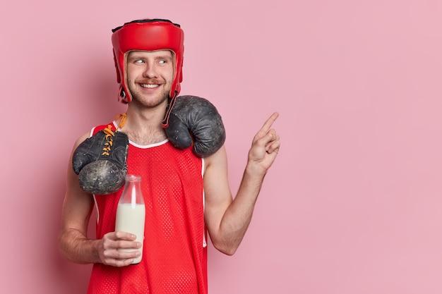 Allegro pugile vestito con abiti sportivi beve latte come fonte di proteine trasporta guantoni da boxe intorno al collo indica nello spazio vuoto della copia