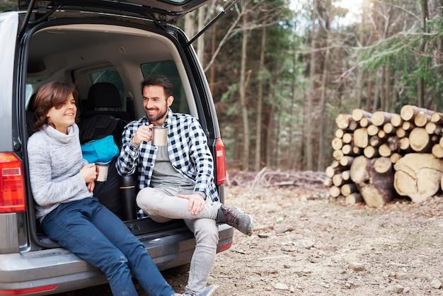 春のハイキング旅行中にお茶を飲む陽気な少年と彼のお父さん