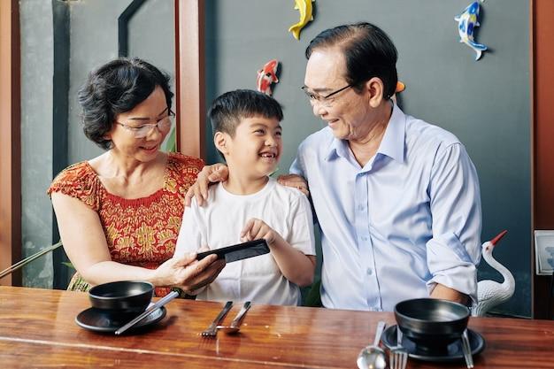 Веселый мальчик в кафе с бабушкой и дедушкой