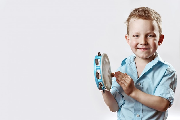 A cheerful boy in a blue shirt holding a tambourine and smiling on a light background