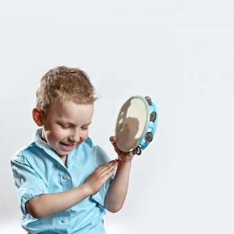 A cheerful boy in a blue shirt holding a tambourine and smiling
