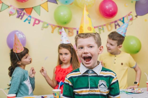 Cheerful boy celebrating birthday with friends