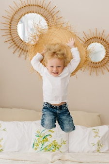 Cheerful boy and galloping with a straw hat on his head on the bed at home. stylish interior with mirrors.