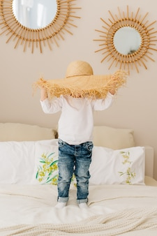Cheerful boy galloping with a straw hat on his head on the bed at home.