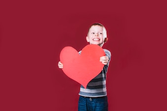 Cheerful boy giving heart