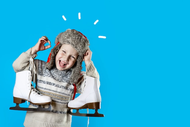 Cheerful boy in a hat with earflaps holding ice skates on blue background