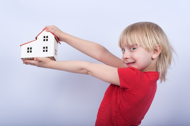 Cheerful boy holding model house and laughs. portrait of child with toy house in hands on white background.