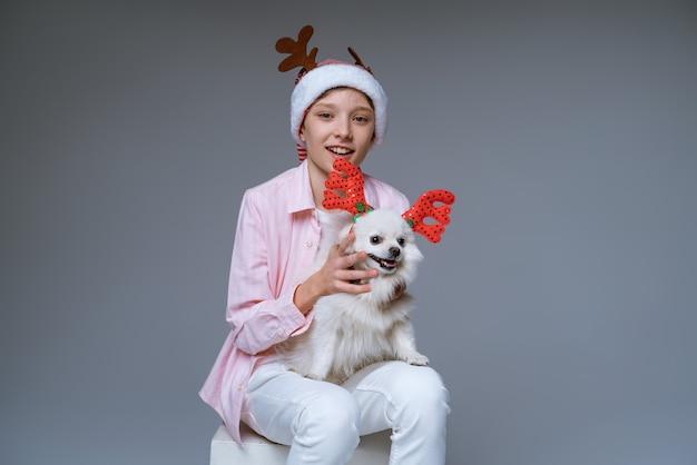 Веселый мальчик в шляпе с оленьими рогами держит на руках собаку, которая тоже с оленьими рогами на свету ...
