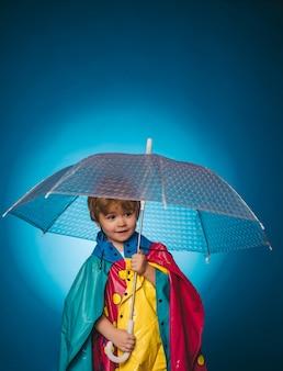 カラフルな傘とレインコートの陽気な男の子。かわいい男の子は秋の準備をしています。雨の中の子供。秋のコレクション全体のセール、信じられないほどの割引と素晴らしい選択。
